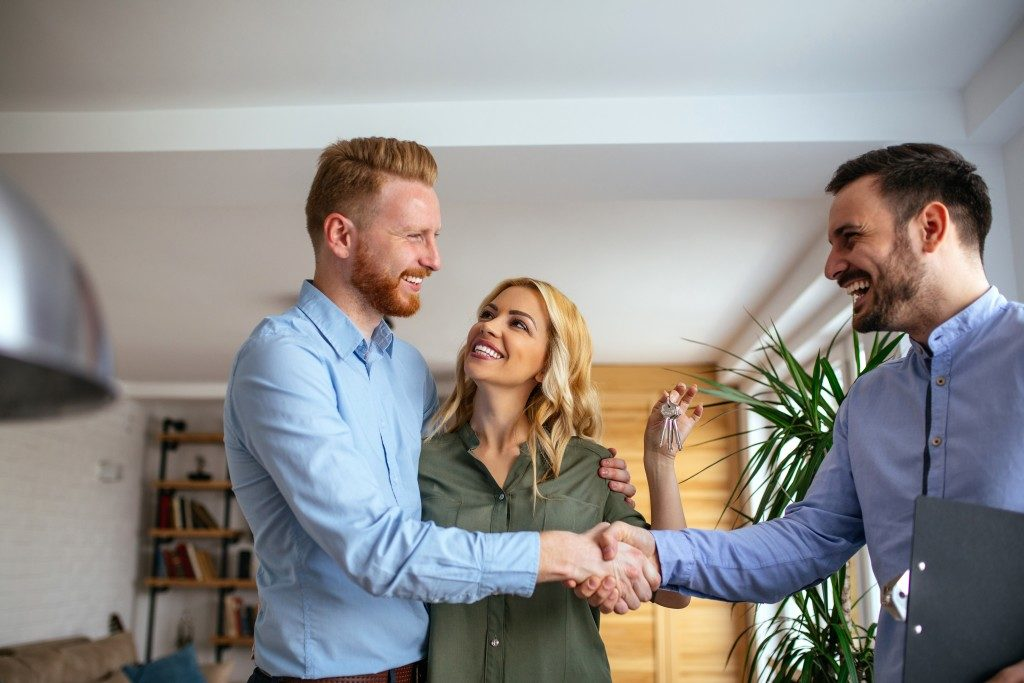 Couple shaking hands of agent while holding new house keys