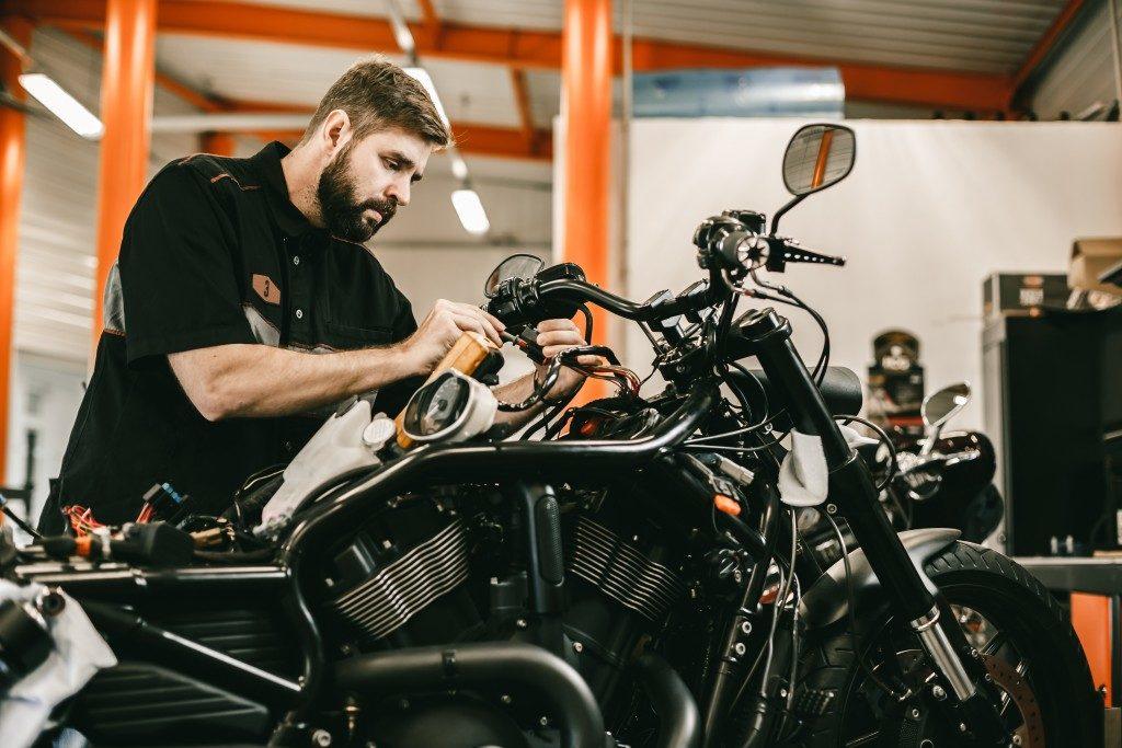 Man repairing electronics sports black bike