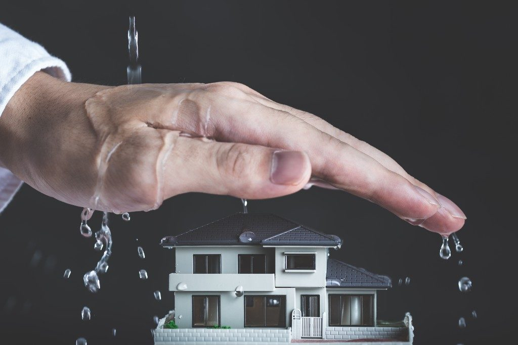 hand covering a miniature house from the water