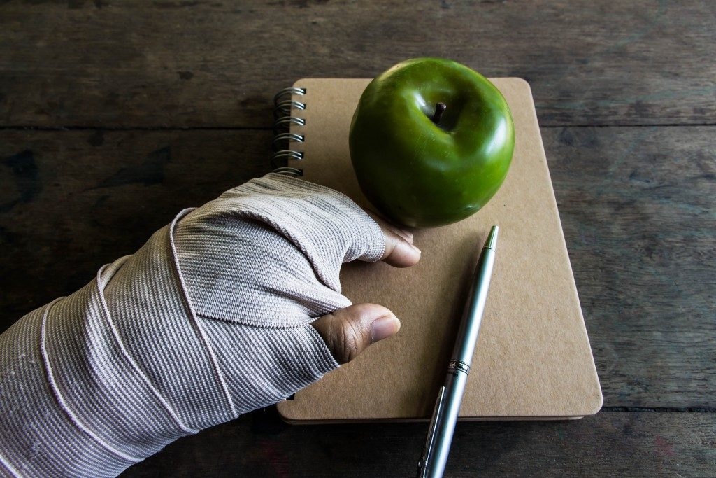 bandaged hand, apple, and notebook