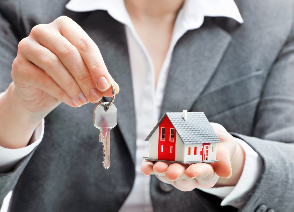 woman holding house model and keys